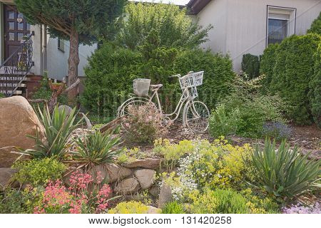 Old white bicycle in the garden as decoration