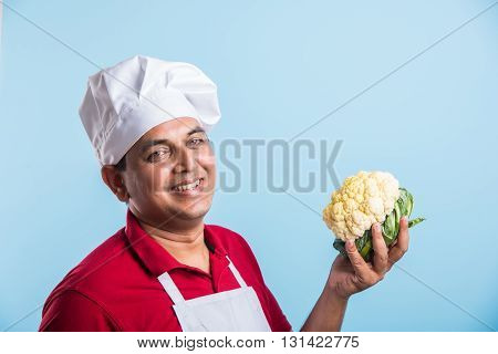 indian male chef holding Cauliflower, standing isolated over blue background, asian male chef holding Cauliflower