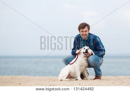 Handsome man, dressed in a blue plaid shirt and blue jeans plays in the spring on a sandy beach near a calm blue ocean with his faithful friend, a dog breed Golden Retriever
