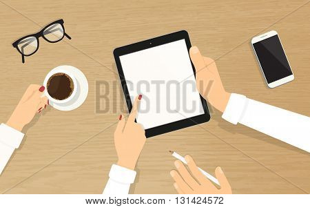 Human hands hold a blank tablet pc with empty display and showing something to his colleague. Top view of realistic wooden table on the office with grasses, smartphone and coffee cup