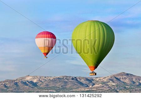 Hot air balloons over mountain landscape in Cappadocia Goreme National Park Turkey