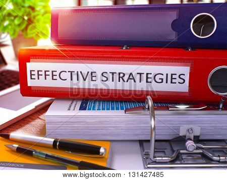 Red Ring Binder with Inscription Effective Strategies on Background of Working Table with Office Supplies and Laptop. Effective Strategies Business Concept on Blurred Background. 3D Render.