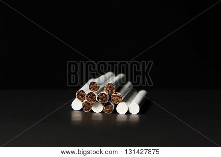 several thin white filter cigarettes on a black background