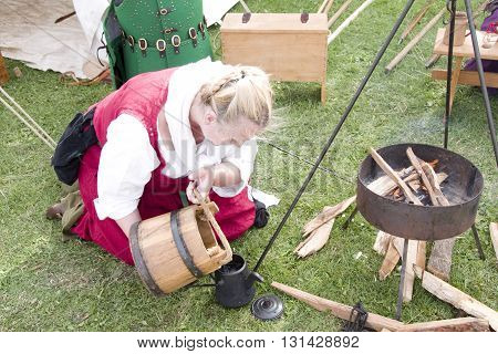 Tewkesbury, UK-July 17, 2015: Historical Reenactor makes tea at the Living History Camp on 17 July 2015 at Tewkesbury Medieval Festival