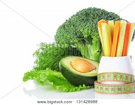 The concept of a healthy eating and weight loss centimeter green vegetables broccoli carrots and avocado isolated on white background