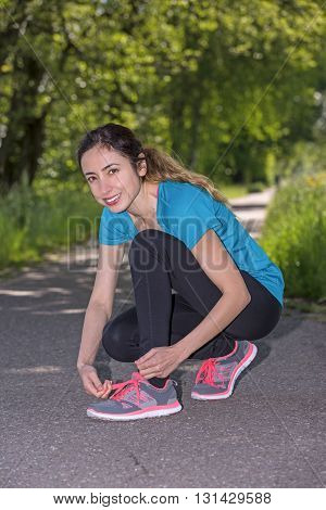 Sporty woman binding her shoes before running.