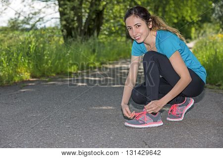 Sporty woman binding her running shoes outdoors before jogging