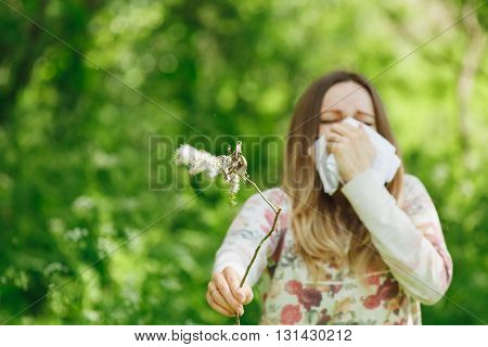 young woman suffering spring pollen allergy. Sneezing into a white handkerchief, holding a sprig with fuzz.
