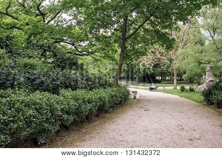 PARIS FRANCE - MAY 14 2013: This is secluded alley Luxembourg Gardens with a few people resting.