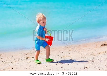 Little baby boy wearing blue rash guard suit playing on tropical ocean beach. UV and sun protection for young children. Toddler kid building sand castle during family sea vacation. Summer water fun.