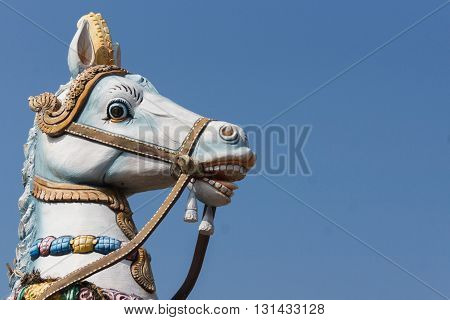 Chettinad India - October 16 2013: Decorated head of Ayyanar his white horse against blue skies. Ayyanar is the village protector here the Kadiapatti village.