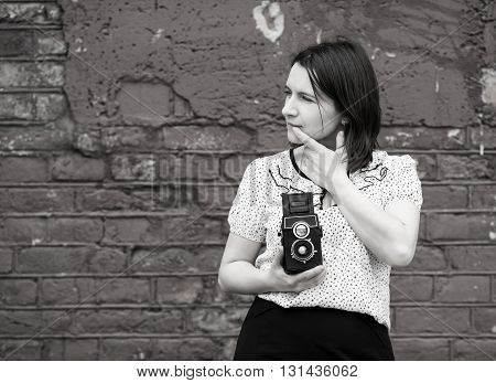 Woman photographer with retro camera in hand. Girl is thinking and looking away. Monochrome image. Old vintage grunge wall in the background. Selective focus on the model.