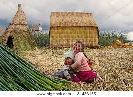 TITICACA PERU MARCH 19 2015: Children in traditional village on floating Uros islands on lake Titicaca in Peru South America