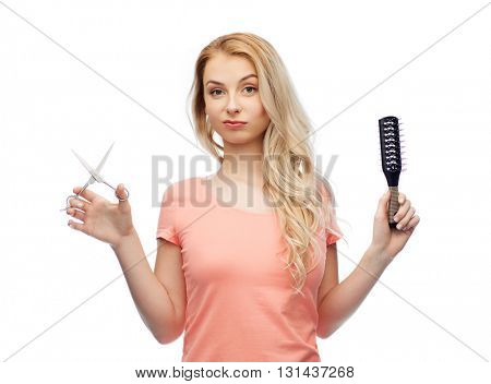 hair care, hairstyle, hairdressing and beauty people concept - young woman or teenage girl with scissors and hairbrush