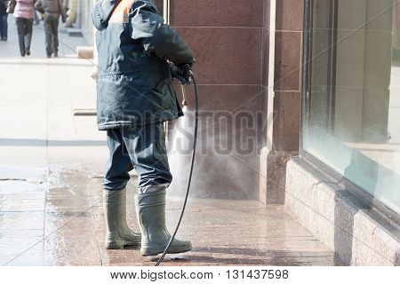 The Person Washes The Sidewalk From A Hose Before Show-window Of Shop