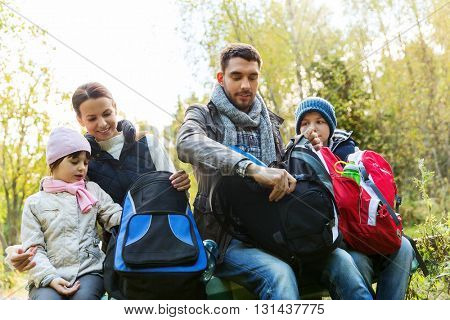 camping, travel, tourism, hike and people concept - happy family with backpacks at camp