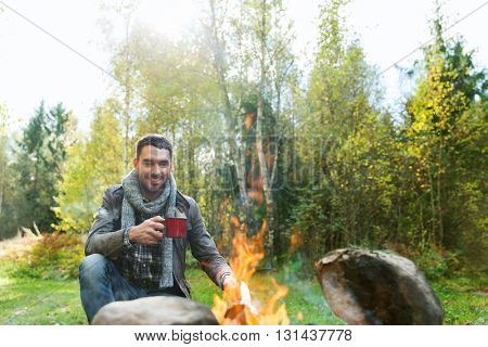 camping, travel, tourism, hike and people concept - happy man drinking hot tea near camp fire at camp in woods