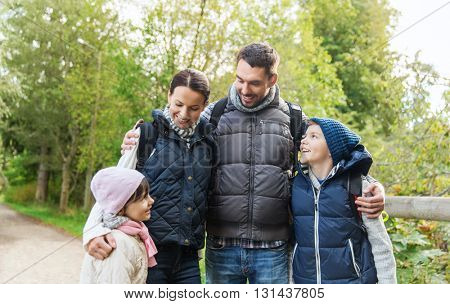 adventure, travel, tourism, hike and people concept - happy family with backpacks in woods