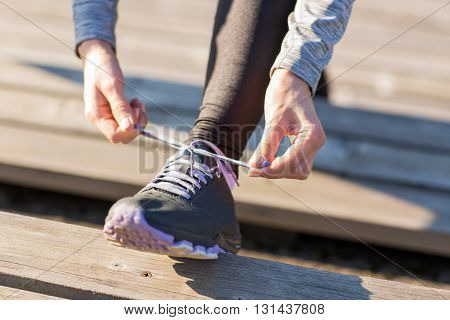fitness, sport, people and lifestyle concept - close up of young sporty woman tying shoelaces outdoors