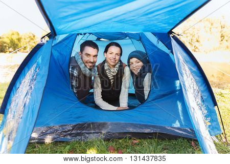 camping, tourism, hike and people concept - happy family inside tent at camp site
