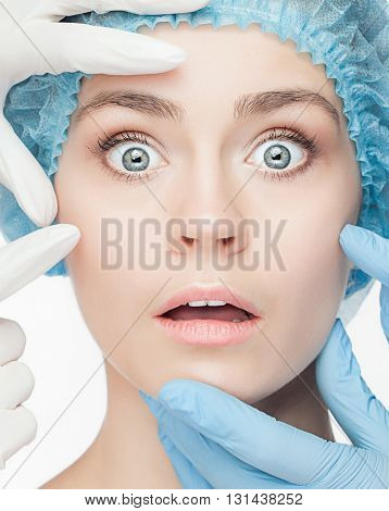 Plastic surgery concept. Doctor hands in gloves touching the surprised and slightly frightened face of woman