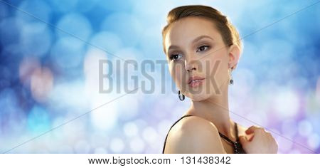 beauty, jewelry, people and luxury concept - face of beautiful young asian woman with earring over blue lights background