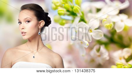 beauty, jewelry, wedding accessories, people and luxury concept - beautiful asian woman or bride with earring and pendant over natural spring lilac blossom background