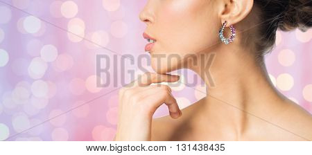 glamour, beauty, jewelry and luxury concept - close up of beautiful woman face with earring over pink holidays lights background