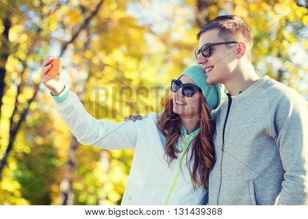 season, vacation, holidays, technology and friendship concept - smiling couple with smartphone taking selfie over autumn park background