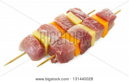 Raw pork skewers with fresh vegetables isolated on white background.