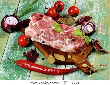 Perfect Raw Pork Neck on Wooden Cutting Board with Arrangement of Spices Herbs Tomatoes Red Onion and Fresh Chili Pepper closeup on Cracked Wooden background