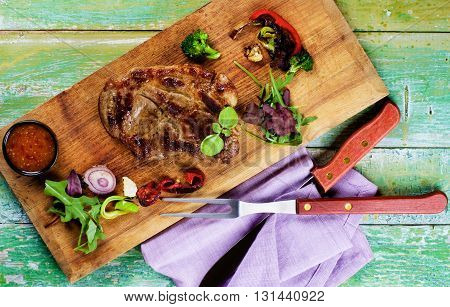 Delicious Roasted Pork Neck with Grilled Vegetables Fresh Greens and Hot Sauce closeup on Wooden Cutting Board with Meat Fork and Knife. Top View