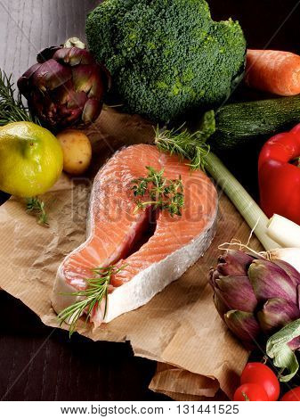 Perfect Raw Steak of Salmon on Parchment Paper and Arrangement of Raw Vegetables with Broccoli Artichokes Spring Onion Tomatoes and Lemon closeup on Dark Wooden background