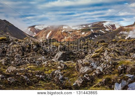 In the hollows of the mountains from the ground rises steam. Rhyolite mountains surround the valley.  Summer morning in the National Park Landmannalaugar, Iceland