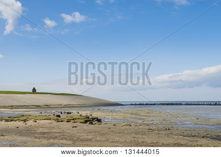 Coastline of the Waddensea at Friesland with mud flats dike and protection poles and dikes. In the background the church of Wierum.