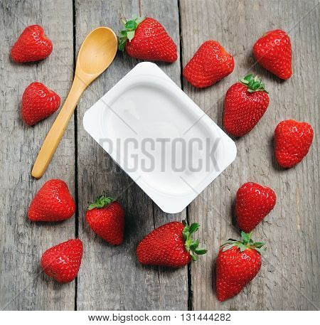 Fresh strawberries and milk yogurt on a wooden table