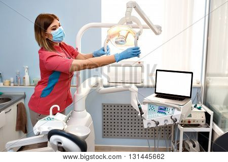 Girl Dentist Prepares The Equipment For Operation. On The Table Is A Laptop With Empty Blank