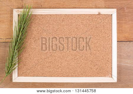 The cork board on the plank wood with the fake pine