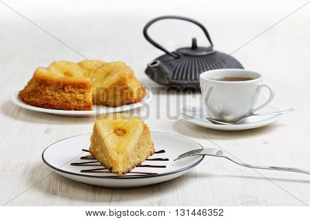 Piece of pineapple Upside Down Cake teapot and cup of tea on white wooden table. Shallow focus.