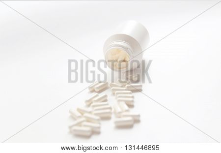 White big Pills in the jar capsules are on the white background