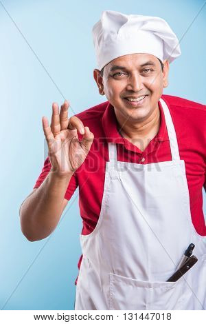 Portrait of a smiling indian male chef cook showing ok sign isolated on a white background, asian male chef and ok sign