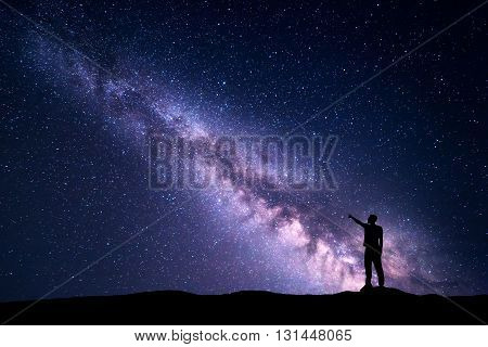 Milky Way with silhouette of a standing young man pointing finger in night starry sky on the mountain. Night landscape. Beautiful Universe travel background with purple sky full of stars
