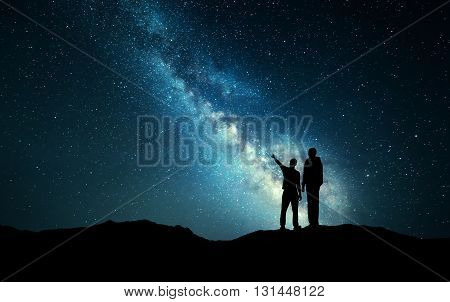Landscape With Milky Way. Silhouette Of A Father And Son