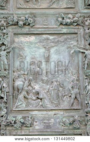 PISA, ITALY - JUNE 06, 2015: The Crucifixion of Jesus Christ, sculpture panel from Giambologna's school, right portal of the Cathedral St. Mary of the Assumption in Pisa, Italy on June 06, 2015