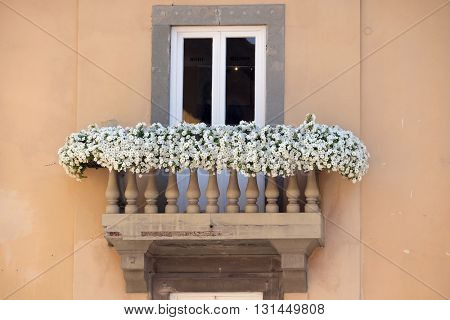LUCCA, ITALY - JUNE 06, 2015: Old house with flowers on balcony in Lucca, Italy, on June 06, 2015