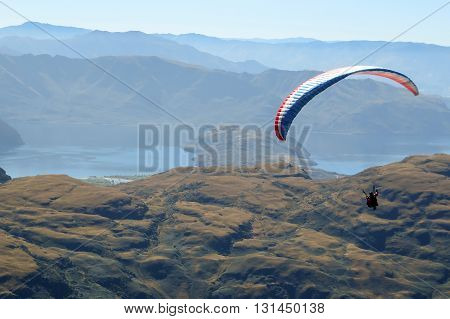 Paragliding sportsman flying high over mountains with a parachute