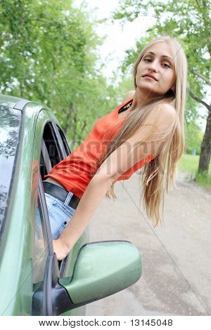 Cheerful young woman having summer trip on a car.