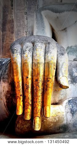 Close up hand of Buddha statue with gold leaf