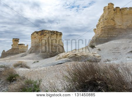 Three blocks of limestone rest in a dry location with brush in the foreground.