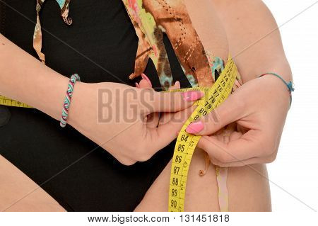 A woman is measuring her waist in a gym